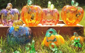 Glass pumpkins on wooden display