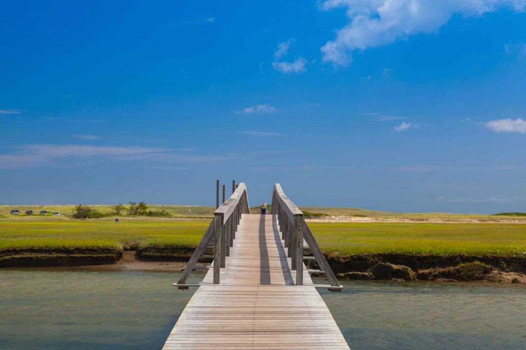 Walkway to the dunes wooden walkway extends over marshland toward the distant dunes and ocean In Sandwich, Cape Cod, Massachusetts,