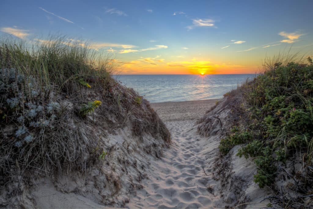 A path through the dunes to Race Point Beach, on Cape Cod near Provience Town MA. Sunset over the water