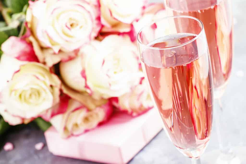 Bouquet of white and red roses, gift box, glasses with pink champagne for a pair of lovers for St. Valentines Day, gray background, selective focus