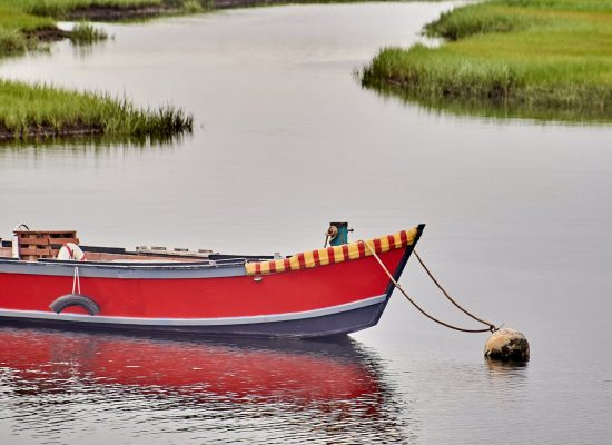 Small red wooden boat moored in Cape Cod, Massachusetts