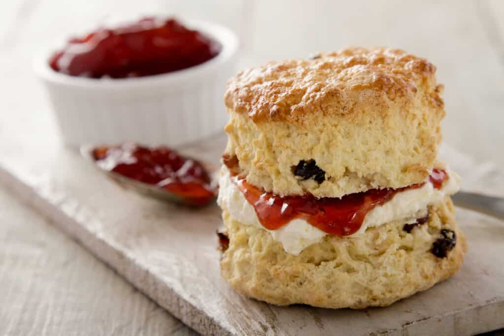 baked scone cut on half spread with whipped cream and strawberry jam