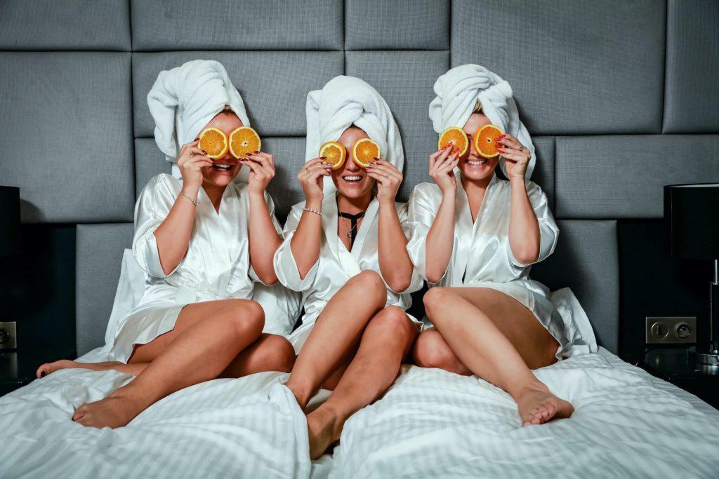three girls in bed holding orange slices