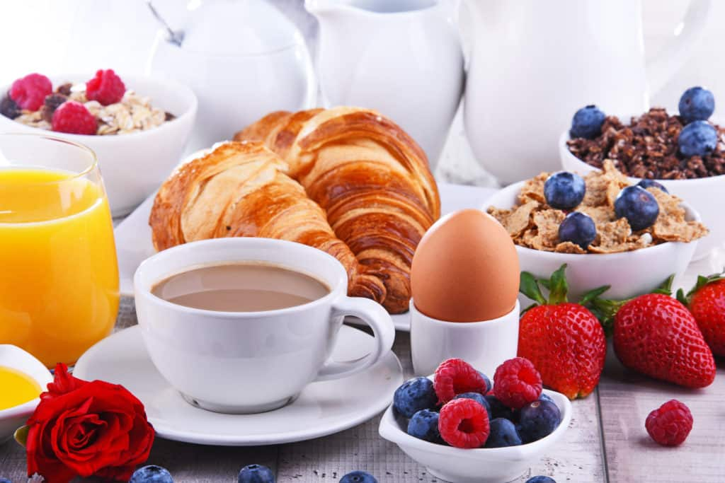 Breakfast served with coffee, orange juice, croissants, egg, cereals and fruits.