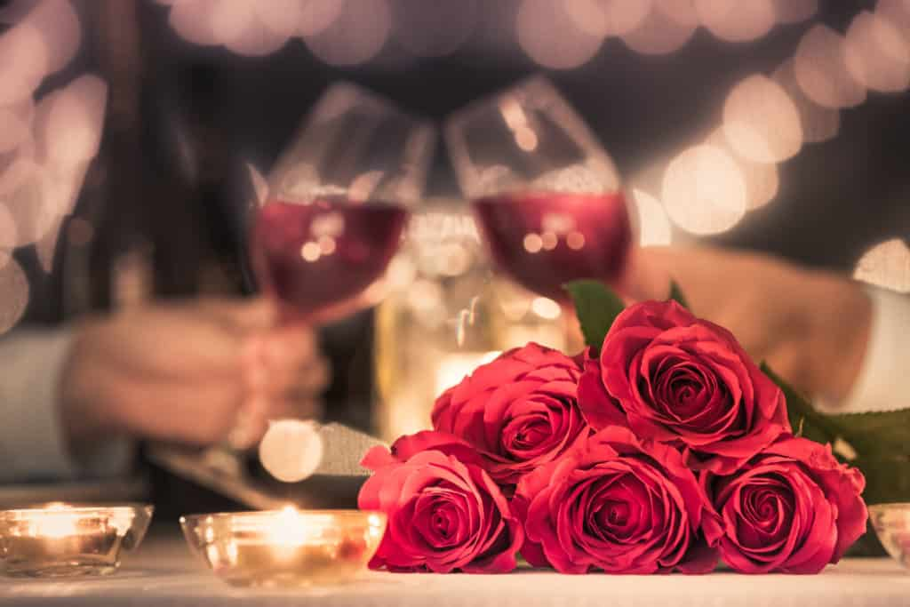 red roses, two glasses of red wine, romantic dinner