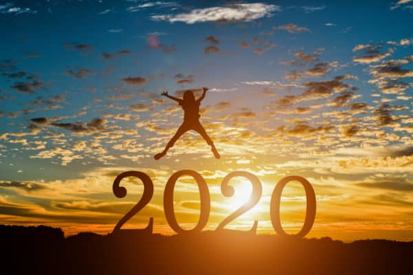 Silhouette young woman jumping to Happy new year 2020 in sunset background.