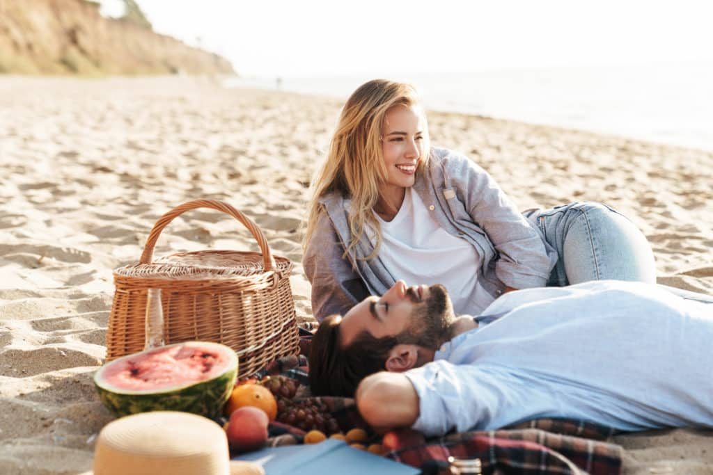 Lovely young couple having a picnic at the beach, laughing