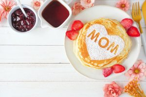 Pancakes with heart shape and MOM letters. Mothers Day breakfast concept. Above view corner border on a white wood background.