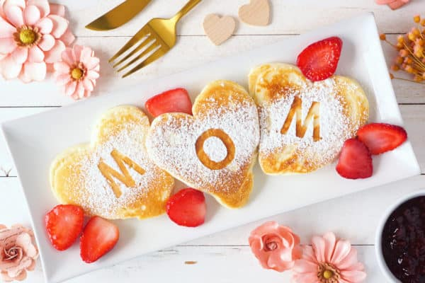 Heart shaped pancakes with MOM letters. Mothers Day breakfast concept. Top view table scene with a white wood background.