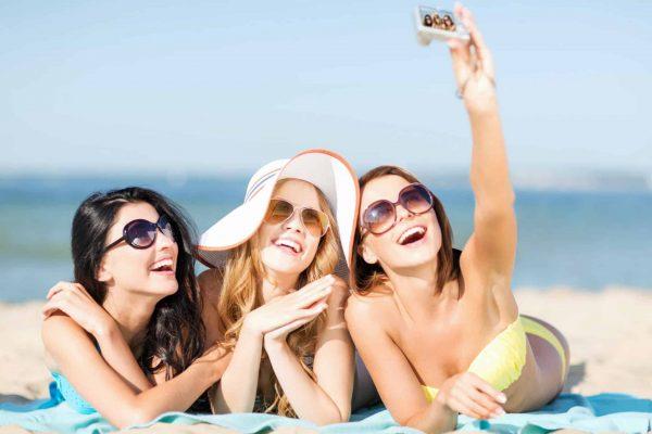 girls taking self photo on the beach