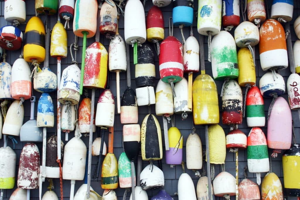 A group of lobster buoys hanging on the side of a building in the harbor of Provincetown, Massachusetts