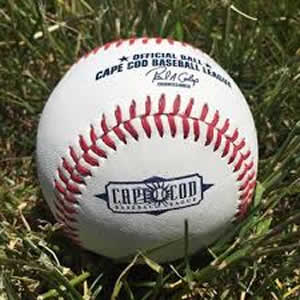close-up view of a white baseball with red stitching and blue lettering that says Cape Cod Baseball sitting in the grass