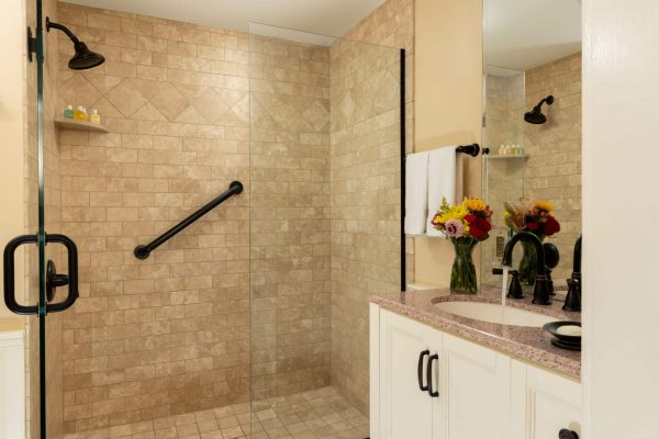 Light brown stone step in shower with white vanity