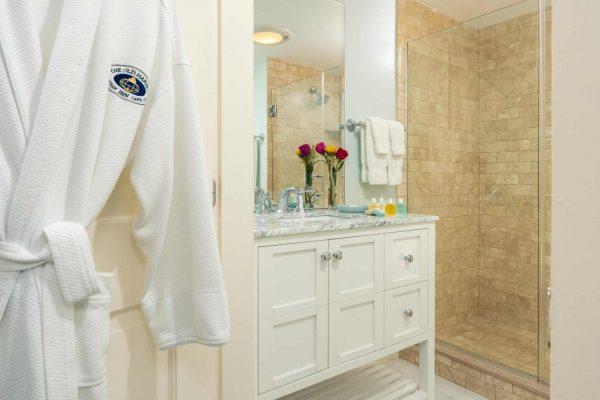 Bathroom room Eastham bathrobe hanging on the door, white vanity, and step in shower