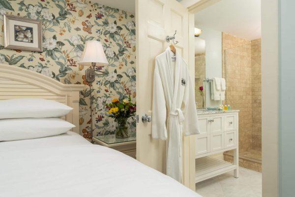 Bathroom room Eastham bathrobe hanging on the door, white vanity, and step in shower.