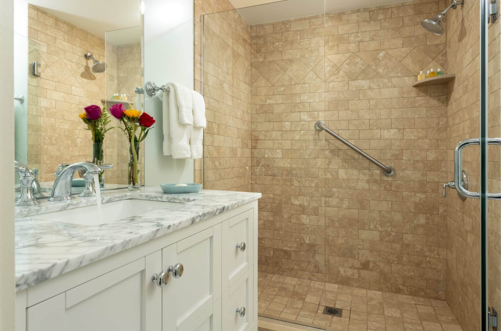 Step in light brown stone shower and white vanity
