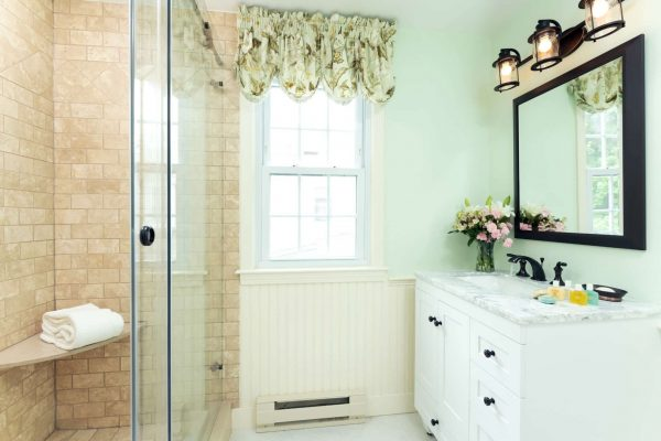 Vanity in room South Beach, large mirror above, glass shower door, and a window