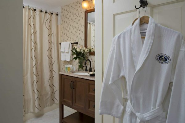 Beige bathroom with paper wall, tub-shower, furniture styled vanity with sink top and white robe