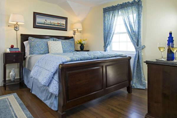 Charming yellow guest room with vaulted ceilings, sunny window, wood floors and wood sleigh bed with colonial blue bedding