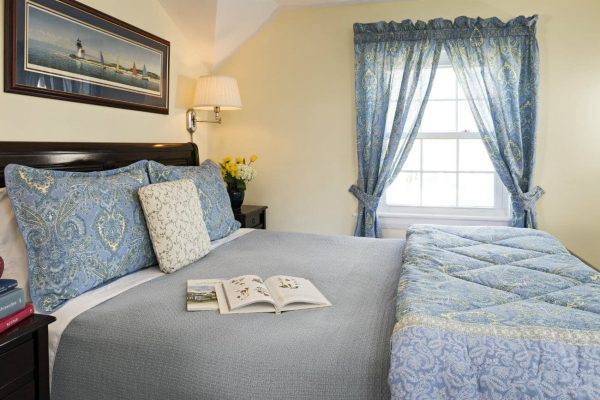 Guest room with pale yellow walls, vaulted ceilings, sunny window, and bed topped with light blue bedding