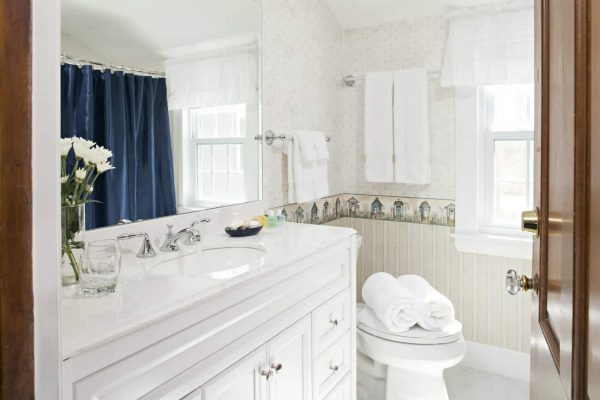 hiny bathroom with white vanity and sink top, large mirror, white stool, sunny window and white towels