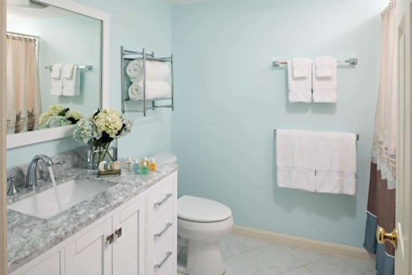 Light aqua bathroom with white vanity, gray and white sink top, white stool and white towels