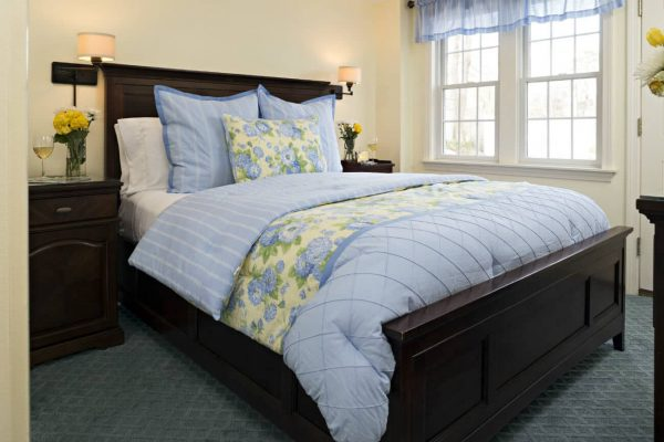 Pale yellow guest room, dark stained bed topped with periwinkle and yellow bedding, two nightstands, and double window
