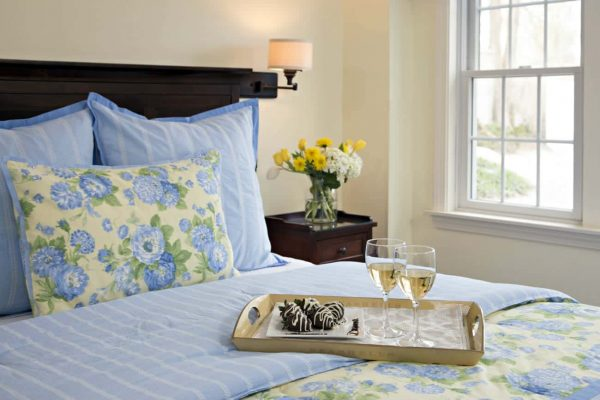 Guest bed topped with periwinkle and yellow bedding and tray of white wine glasses and chocolate covered strawberries