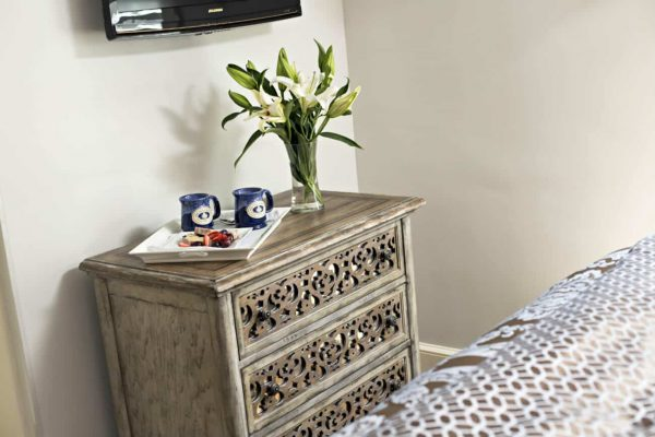 close-up view of light wood chest with decorative drawers topped with fresh flowers and tray of mugs and dessert