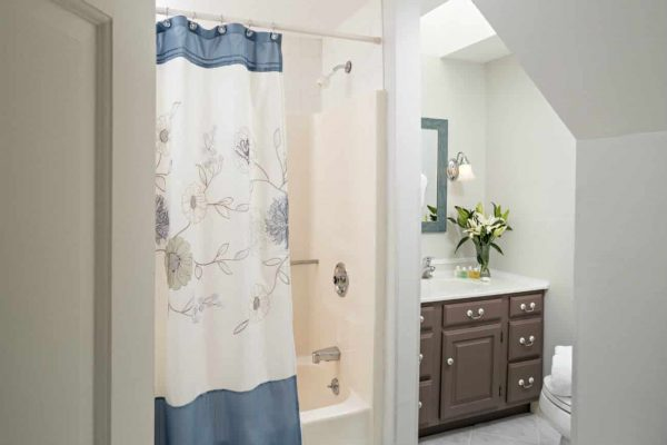 Beige bathroom with vaulted ceilings, tub-shower, brown vanity with white sink top and fresh flowers