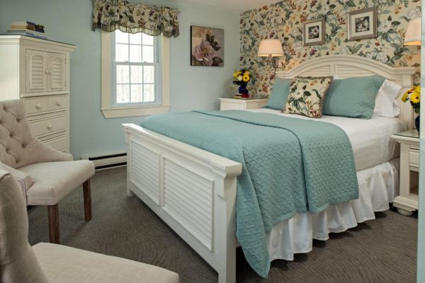 Light blue guest room, one floral papered wall, white bed with white and aqua bedding, armoire and two chairs