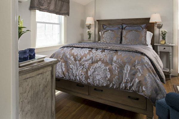 Beige guest room with wood floors, bed with shiny brown and blue comforter, matching night stands and sunny window