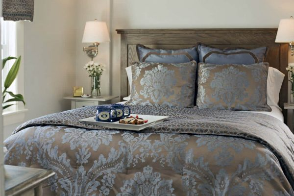 Wood bed topped with shiny brown and blue bedding and pillows, matching nightstands, and tray of two mugs with dessert