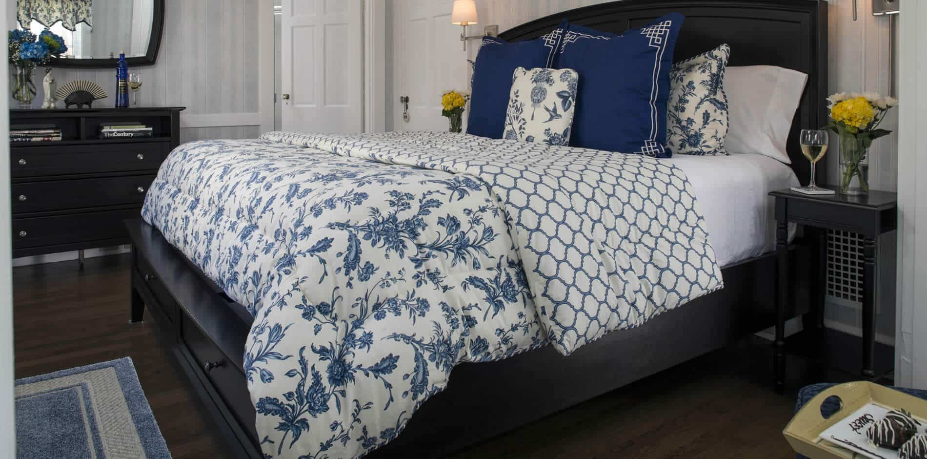 Elegant guest room with dark brown sleigh bed, blue and white bedding, wood floors, and dresser with mirror
