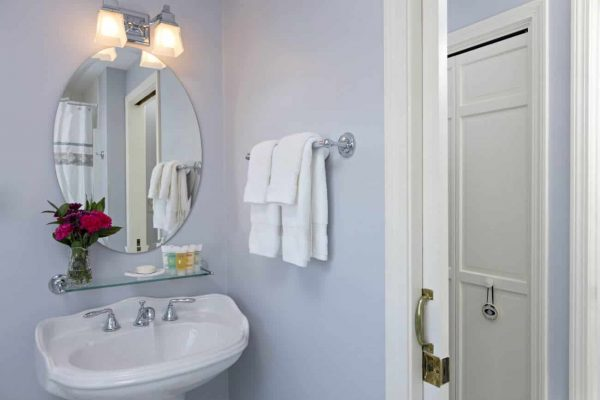 Lilac bathroom with white pedestal sink, oval mirror, white towels and fresh flowers