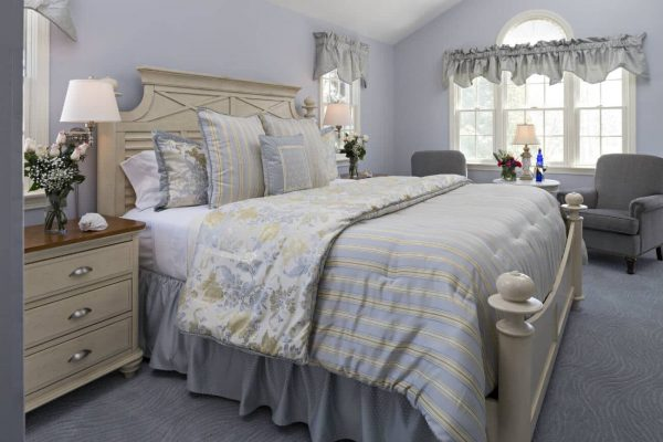 Soft blue guest room, carpeted, ivory bed topped with blue and yellow bedding, vaulted ceilings and several windows