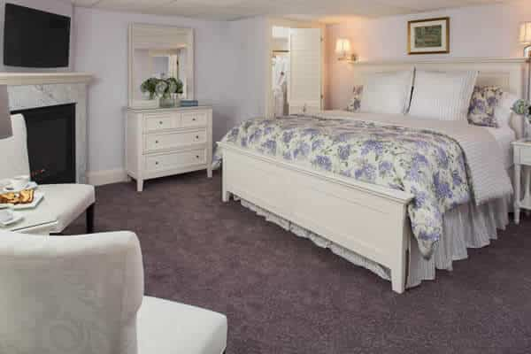 Peaceful lilac guest room with carpet, white furniture, floral bedding, flat screen TV and corner gas fireplace