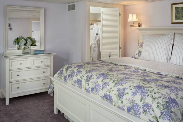 Peaceful lilac guest room, white dresser, white bed topped with purple floral bedding and glimpse of white robe in the closet