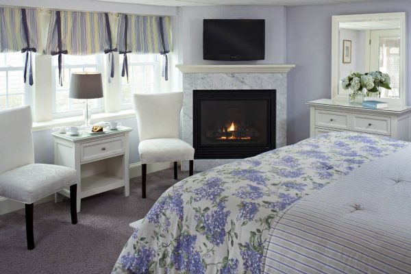 Peaceful lilac guest room with natural light, corner gas fireplace, white furniture and floral and striped bedding
