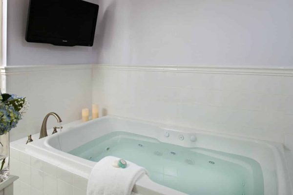 Wide white bathtub with jets, two lit candles, a white towel, and a TV on the wall