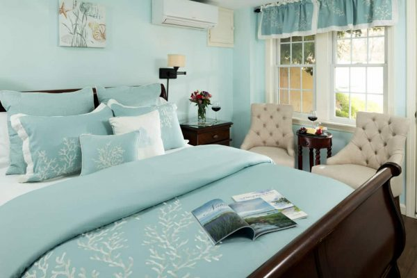 Aqua guest room with cherry sleigh bed topped with aqua bedding and pillows, two beige chairs in front of double window