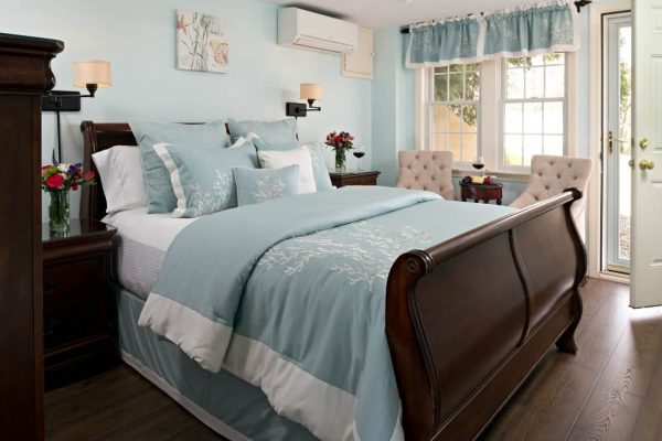 Light aqua guest room with cherry sleigh bed, aqua bedding, double window, wood floors, and exterior door
