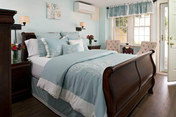 Light aqua guest room with cherry sleigh bed, aqua bedding, double window, wood floors, and exterior door