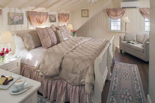 Spacious serene guest room with creamy walls, vaulted ceilings, wood floors, large bed and love seat