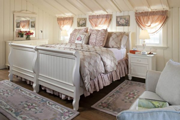 Beautiful soft pink guest room with vaulted ceilings, creamy paneled walls, three sunny windows and wood floors
