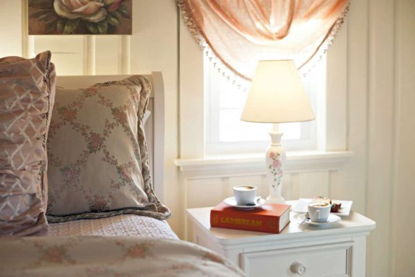 Close-up view of guest bed topped with soft floral bedding next to a white nightstand in front of a sunny window