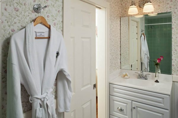 Bathroom with walls papered in soft green and rose, white vanity and sink with mirror and white bathrobe