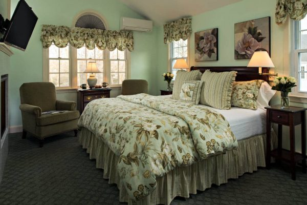 Light green guest room, vaulted ceilings, bed topped with floral and striped bedding, several windows, upholstered chairs, flat screen tv
