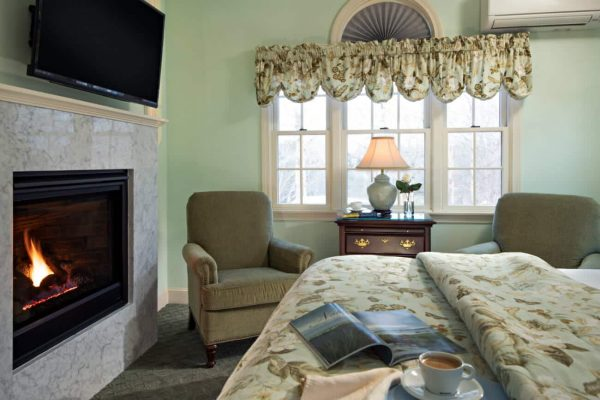 Light green guest room, triple window, two upholstered chairs, flat screen tv, and gas fireplace