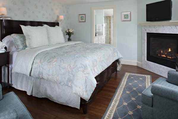 Peaceful light blueish-green guest room with dark brown sleigh bed, corner gas fireplace, flat screen TV and wood floors